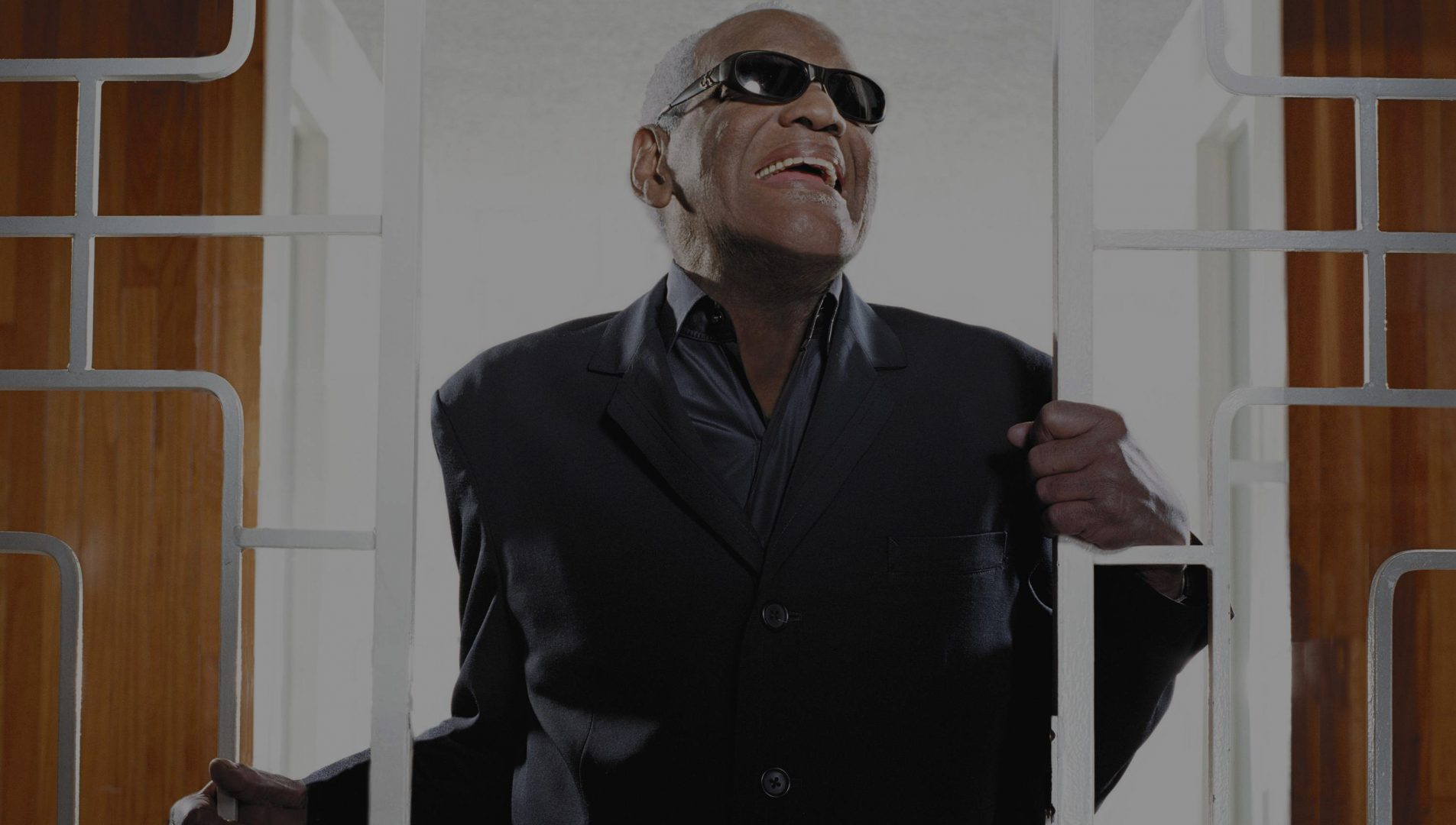 Ray Charles smiling in a collared shirt and sports jacket wearing his trademark sunglasses.